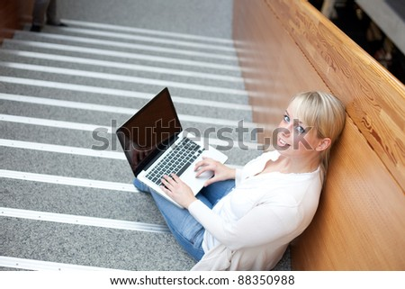 young blond woman with a laptop on the stairs/woman with a laptop - stock photo