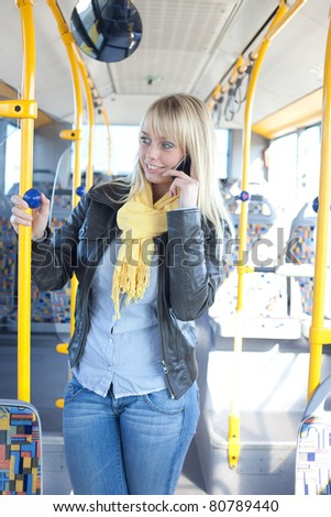young blond woman with a smartphone inside a bus/young blond woman with a smartphone on her ear inside a bus - stock photo