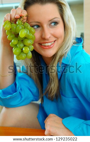 young blond woman with grapes - stock photo