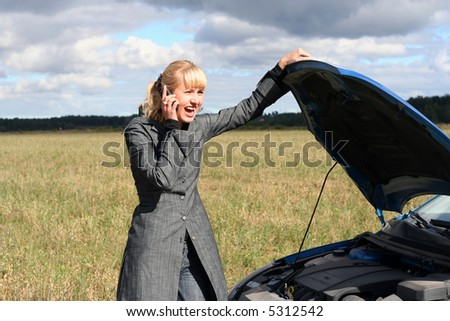 young blond woman with her broken car. The girl is angry - stock photo