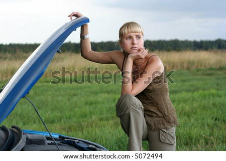 young blond woman with her broken car. The girl is sad - stock photo