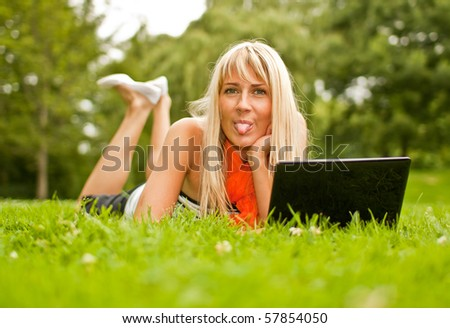 Young blond woman with laptop in the park