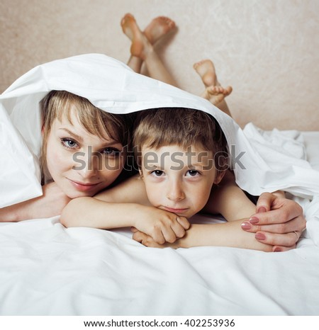 young blond woman with little boy in bed, mother and son, happy familyyoung blond woman with little boy in bed, mother and son, happy family - stock photo