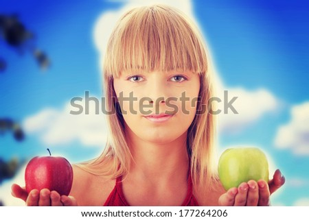 Young blond woman with red and green apples on her hand - making decision concept - stock photo