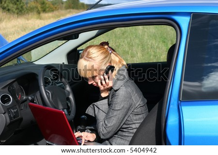 young blond woman with red notebook and mobile phone in a blue car - stock photo
