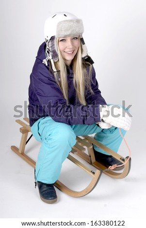 Young blond woman with skiing suit and helmet on a sleigh - stock photo