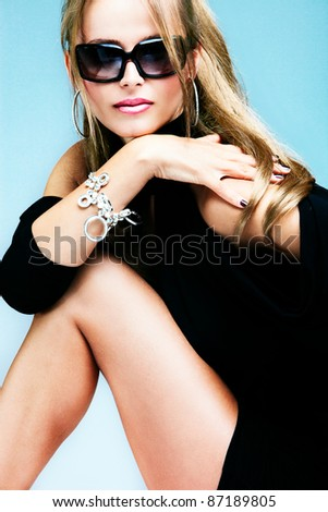 young blond woman with sunglasses, studio shot - stock photo