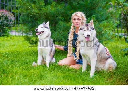 Young blond woman with two Husky dogs sits on grass in summer park.