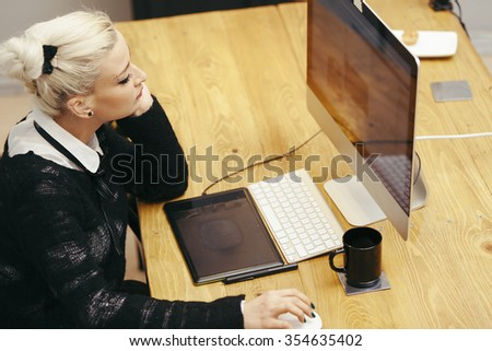 young blond woman working at homely office - stock photo