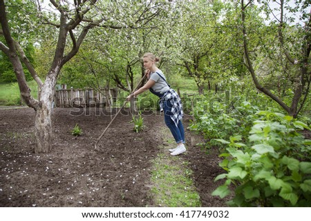 young blond woman working in the home garden with a rake in spring