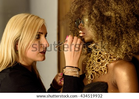 Young blonde artist painting gold lips with tassel, fashion African or Black American model - stock photo