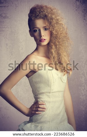Young, blonde, beautiful girl with flufy, curly hairstyle. She is wearing white, gorgeous dress with a loop and colorful makeup.