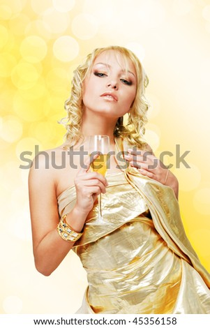Young blonde beautiful woman with champagne glass against golden bokeh background - stock photo