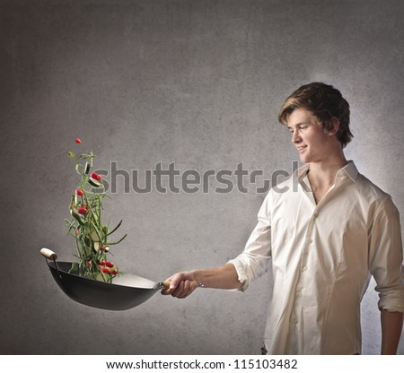 Young blonde boy cooking vegetables with a pan - stock photo