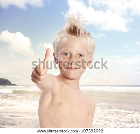 Young Blonde Boy Giving Thumbs Up at the Beach - stock photo