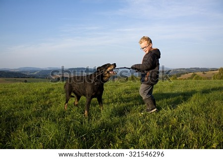 young blonde boy play with old black dog outdoor - stock photo