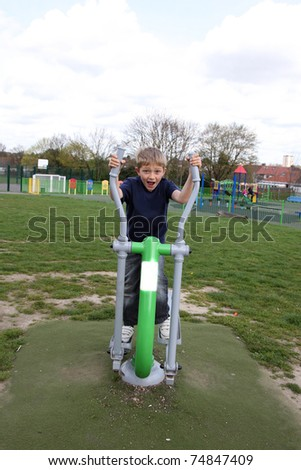 young blonde boy playing on outdoor gym equipment