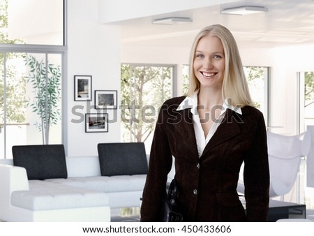 Young blonde caucasian businesswoman at designer home indoors, standing, looking at camera. - stock photo