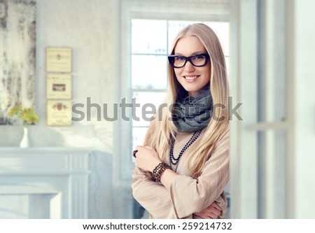 Young blonde caucasian casual artist woman with glasses at vintage home. Standing, smiling, looking at camera, arms crossed. Elegant. - stock photo