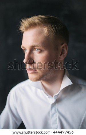 Young blonde dreamy man in white shirt studio portrait