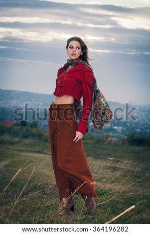 young blonde fashion girl  wearing scarf, long brown skirt and red leather jacket outdoor day shot, stand on top of hill
