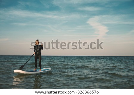 Young blonde female paddles a paddleboard at the sea  - stock photo