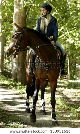 Young blonde female rider horseback riding in the woods. - stock photo