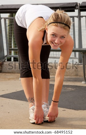 young blonde female stretching outside - stock photo
