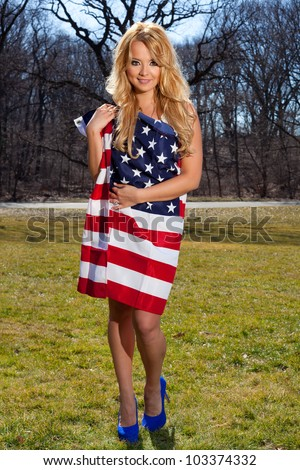 young blonde female wrapped in a american flag in the park - stock photo