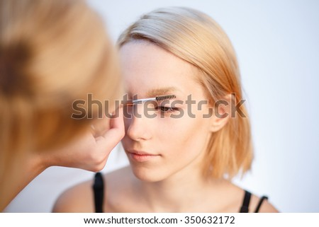 Young blonde girl applying make-up by make-up artist in studio,  - stock photo