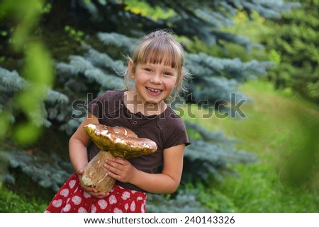 Young blonde girl holding a very large mushroom