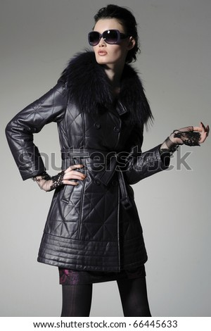 young blonde girl in autumn/winter dress wearing sunglasses posing - stock photo