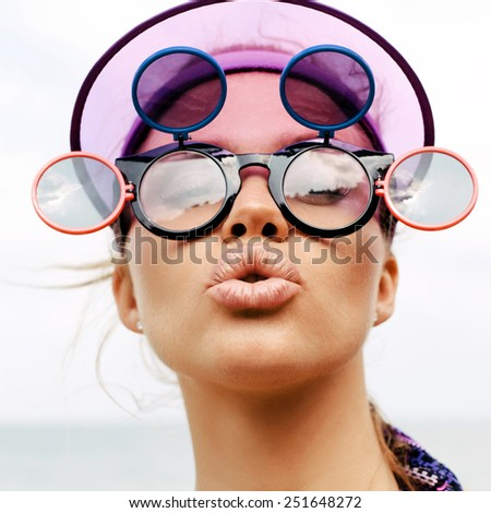 Young blonde girl in sunglasses showing middle finger. Outdoors lifestyle close-up of sexy woman on beach - stock photo