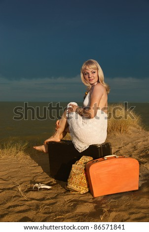 Young blonde girl in white dress sitting on a large suitcase. Next to her other bags. Against the background of dark blue clouds.