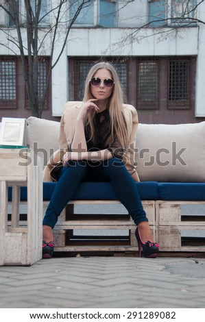 Young blonde girl posing in the street - stock photo