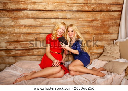 Young blonde girl, sister, communicate in social networks and make funny selfie, holding a tablet computer. The concept of youth and technology. - stock photo