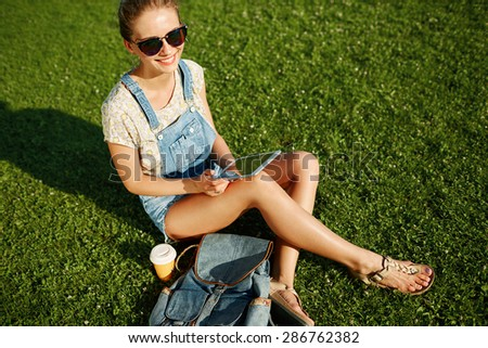 Young blonde girl using tablet outdoor sitting on grass and smiling. Student using digital tablet after school at park.
