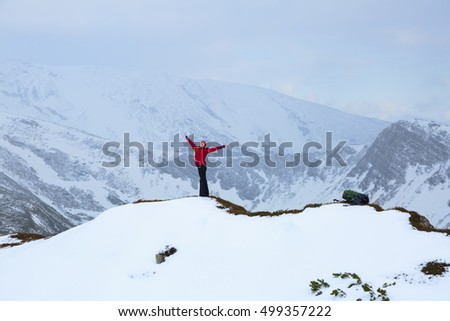Young blonde girl with a red hat goes in for sports in extreme conditions in the mountains on winter sunny day.