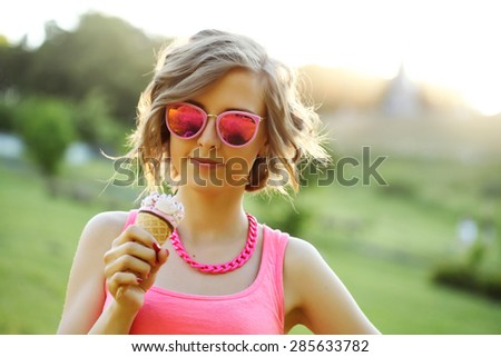 Young blonde hipster girl eating a delicious ice cream in summer hot weather in sunglasses have fun and good mood looking in camera and smiling.  - stock photo