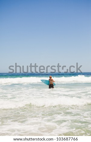 Young blonde man returning to the beach while holding his surfboard - stock photo