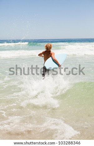 Young blonde man wading in the water while holding his blue surfboard - stock photo