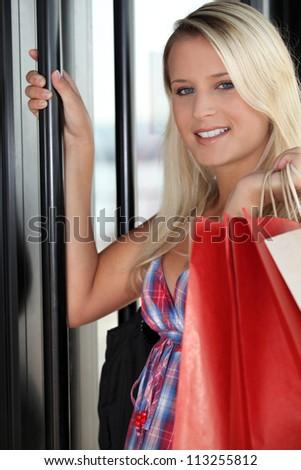 Young blonde opening door - stock photo