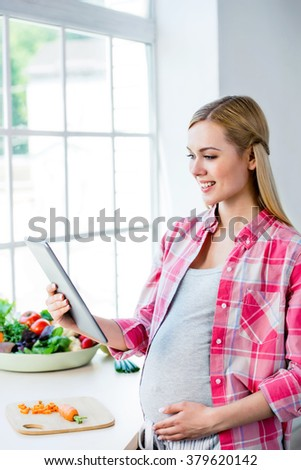 Young blonde pregnant woman cooking in kitchen. Woman making healthy vegetable salad and using tablet computer - stock photo