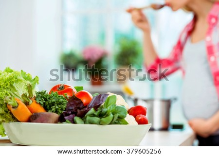 Young blonde pregnant woman cooking in kitchen. Woman making healthy vegetable soup. Focus on plate of vegetables - stock photo
