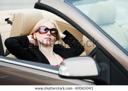 Young blonde sitting in a convertible. - stock photo