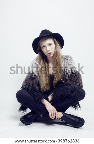 young blonde teenage girl in hat and fur coat, fashion dressed model, studio shot - stock photo