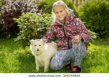 Young blonde teenage girl in jacket play with her dog gently love friends in green garden