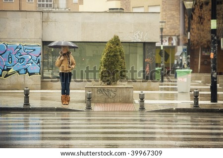Young blonde waiting for the traffic stop under rain - stock photo