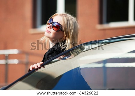 Young blonde with a convertible car. - stock photo