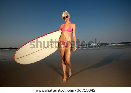 Young Blonde Woman at the beach surfing and enjoying herself - stock photo